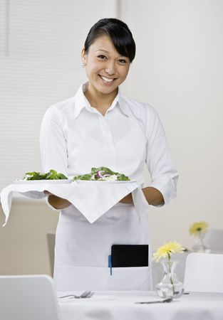 vertically: Young female server with tray of food standing next to table. Vertically framed shot.