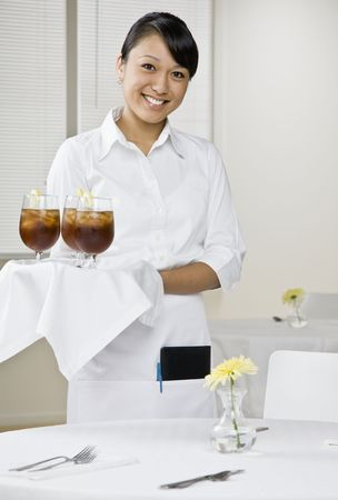 Young female server with tray of drinks standing next to table. Vertically framed shot.