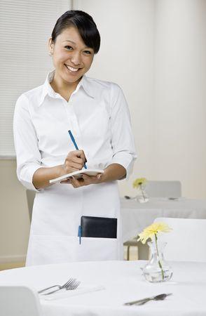 Young female server taking orders. Vertically framed shot.