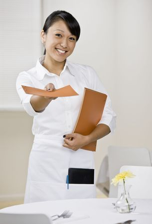 20s waitress: Young female server with menus. Vertically framed shot. Stock Photo