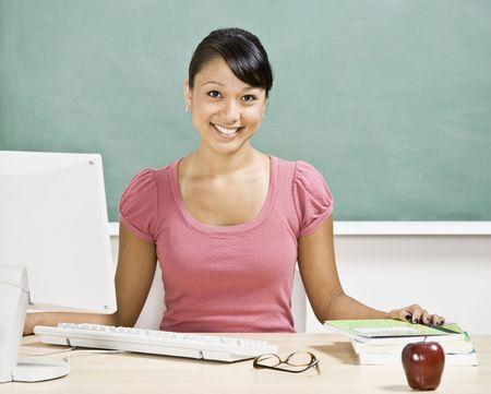 educadores: Joven maestro femenino sentado en la mesa de trabajo en aula. Horizontalmente enmarcado disparo.