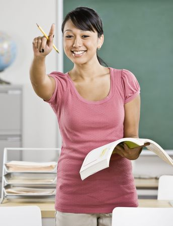 Young female teacher calling on student in classroom. Vertically framed shot.