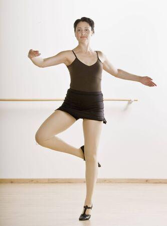 mid adult female: Mid adult female dancer in pose. Vertically framed shot.