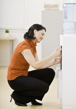kneeling woman: Business woman at water cooler. Vertically framed shot. Stock Photo