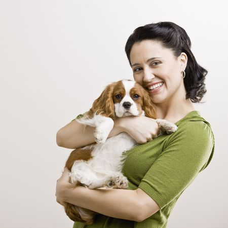 Adult female holding puppy. Square format.