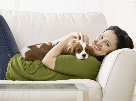woman couch: Woman lying on couch holding puppy. Horizontally framed shot. Stock Photo