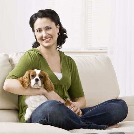 couch: Woman sitting on couch holding puppy. Square format.