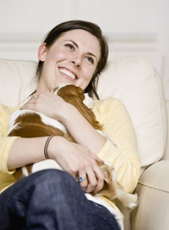 woman on couch: Young woman sitting on couch holding puppy. Vertically framed shot.