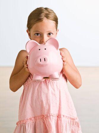 portraiture: Girl holding piggy bank
