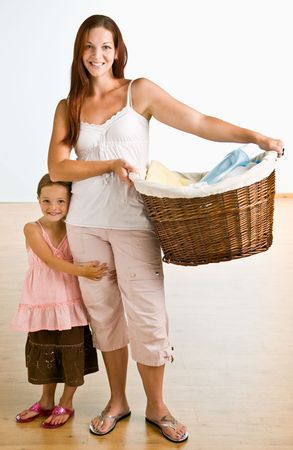 laundry basket: Mother holding laundry basket with daughter near Stock Photo