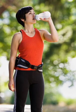 Runner drinking from water bottle photo