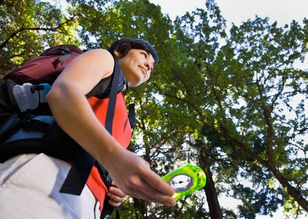 tramping: Woman with backpack using compass Stock Photo