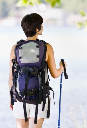 Woman hiking with backpack and walking stick photo