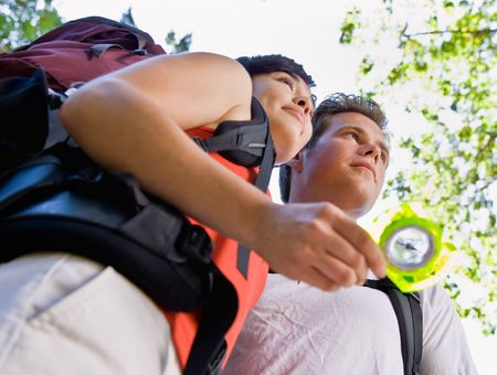 tramping: Couple with backpacks looking at compass