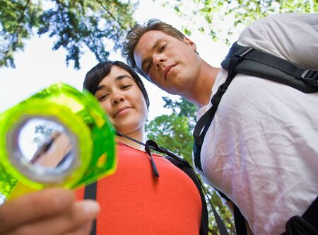 Couple with backpacks looking at compass photo