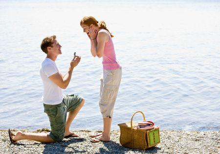 Boyfriend proposing to girlfriend near stream