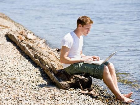 Man using laptop near stream photo