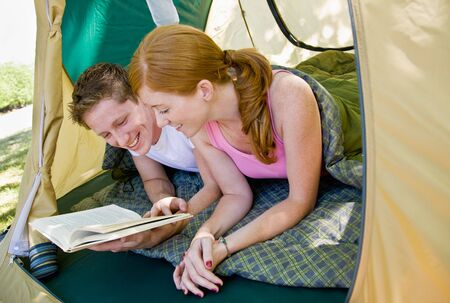 twenty two: Couple laying in tent reading book Stock Photo