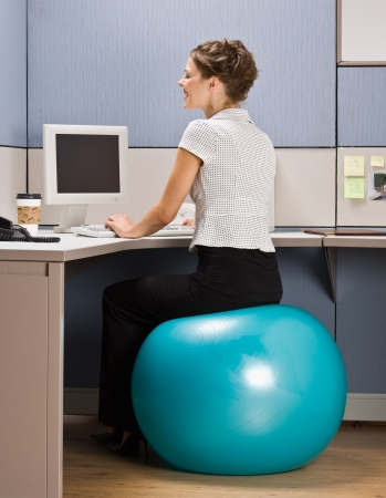 office desk: Businesswoman sitting on exercise ball at desk Stock Photo