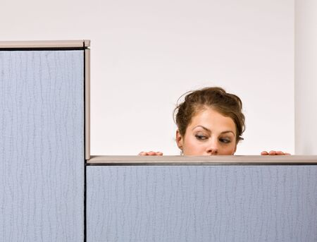 espionage: Businesswoman peering over cubicle wall Stock Photo