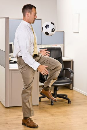 Businessman playing with soccer ball in office photo