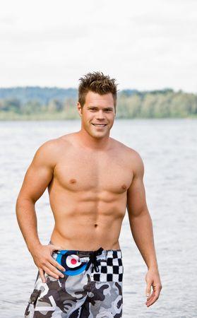 wading: Man in swim trunks wading in lake