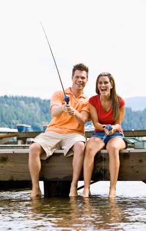 Couple fishing on pier Stock Photo