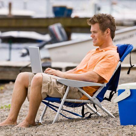 laptop: Man using laptop on beach Stock Photo