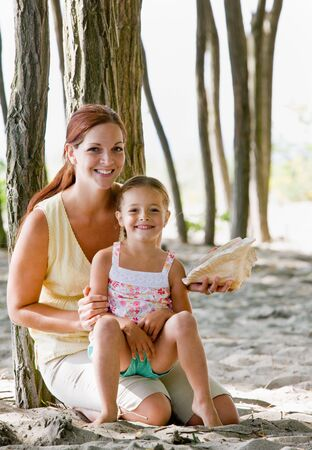Mother and daughter with seashell photo