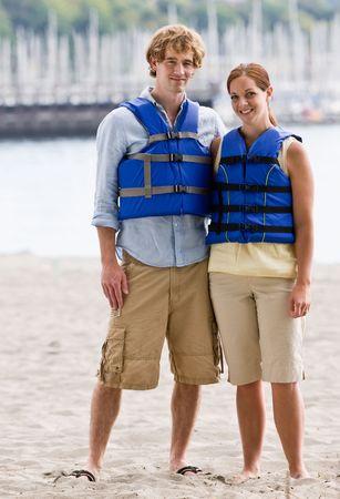 twenty two: Couple wearing life jackets at beach