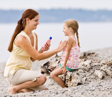 Mother applying sunscreen to daughter at beach photo