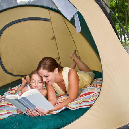 어머니가 텐트에서 딸에게 독서하다 스톡 콘텐츠