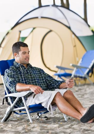 Man using mp3 player at campsite Stock Photo - 6413686