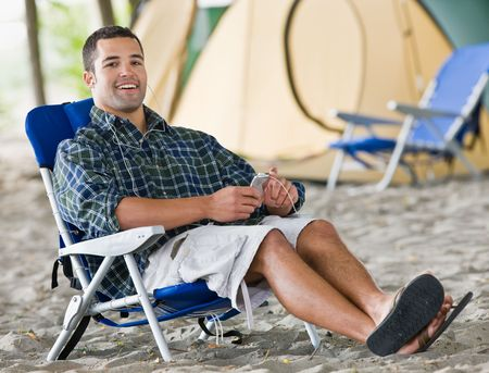 campsite: Man using mp3 player at campsite Stock Photo