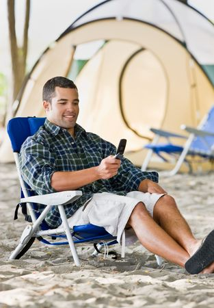 Man text messaging on cell phone at campsite Stock Photo - 6413465