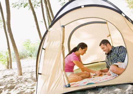 Couple playing boardgame in tent Stock Photo - 6413674