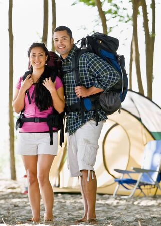 twenty two: Couple carrying backpacks at campsite