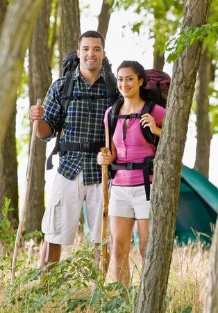 Couple in backpacks hiking photo