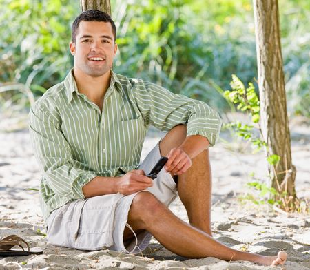 sms: Man text messaging on cell phone at beach Stock Photo