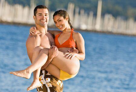 carrying girlfriend: Boyfriend carrying girlfriend at beach