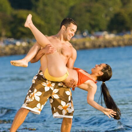 twenty two: Boyfriend lifting girlfriend on beach