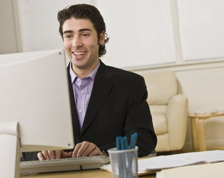 A young businessman is working on a computer.  He is looking away from the camera.  Horizontally framed shot. Stock Photo - 6413830