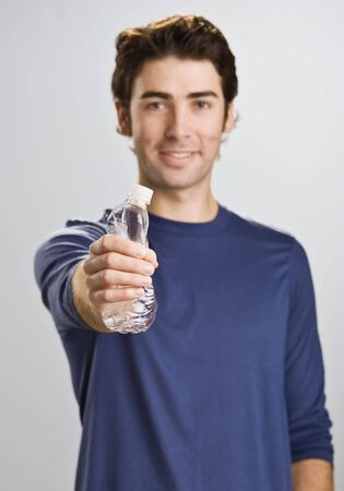 standing water: A young man is standing in a room and cushing a water bottle.  He is smiling at the camera.  Vertically framed shot.