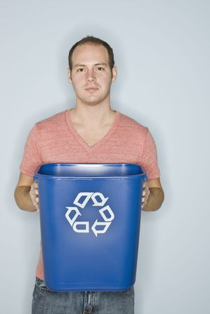 A man is holding a recycling basket.  He is looking at the camera.  Vertically framed shot. photo