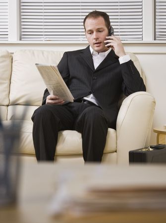 A businessman is seated on a couch and talking on a cellphone.  He is looking away from the camera.  Vertically framed shot. photo