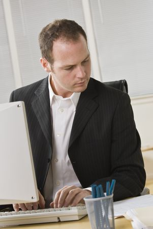A young businessman is working on a computer.  He is looking away from the camera.  Vertically framed shot. photo