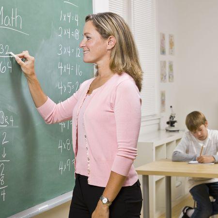 Teacher writing on blackboard photo