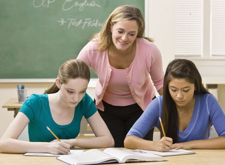 30s adult: Teacher helping students study Stock Photo