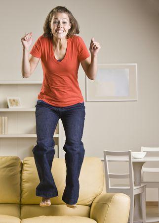 Teenage girl jumping on sofa Zdjęcie Seryjne