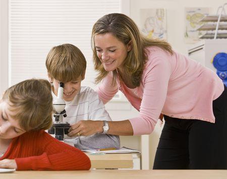 profesor alumno: Profesor ayudar a estudiantes con microscopio